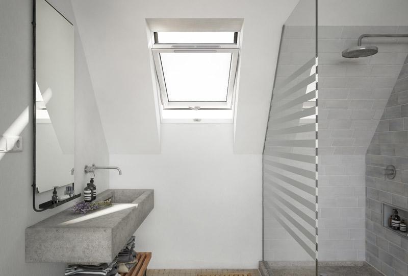 Ein modernes Badezimmer mit Regendusche, Glaswand, Steinwaschbecken und ECOREST Dachfenster von Liteleader.